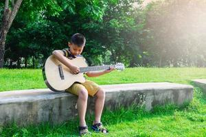 menino tocando violão em um jardim
