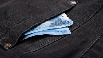 dinheiro no bolso da calça jeans, conceito de despesas financeiras foto