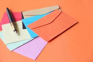 envelopes coloridos e caneta-tinteiro em fundo laranja foto