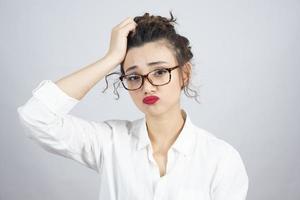 foto de uma jovem mulher de cabelo encaracolado de óculos posando para a câmera