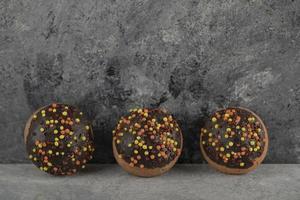 três donuts doces de chocolate com granulado foto