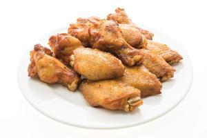 Asa de frango grelhado na brasa em prato branco foto