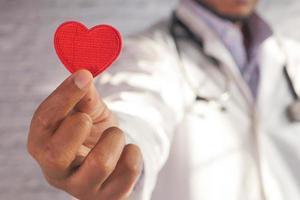 médico segurando um coração vermelho de brinquedo foto