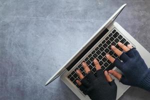 vista superior de mãos usando luvas de dedo, trabalhando em um laptop foto