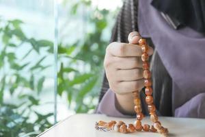 mãos de mulher rezando com contas foto