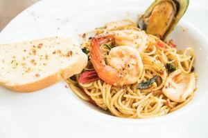 espaguete de frutos do mar em chapa branca foto