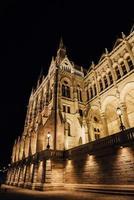 o parlamento húngaro em Budapeste, no Danúbio, à luz noturna dos postes de luz foto