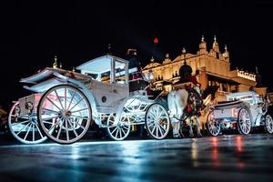 Cracóvia, Polônia 2017 - a antiga praça da noite em Cracóvia com carruagens puxadas por cavalos