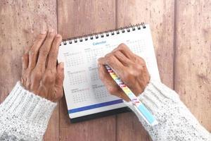mulher marcando dias em um calendário de 2021 foto