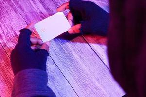homem usando luvas pretas segurando um cartão de crédito branco foto