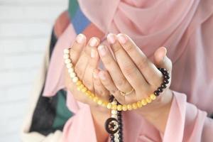 mãos de mulher segurando contas de oração foto