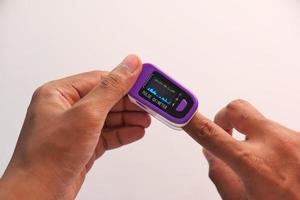 mão de jovem usando oxímetro de pulso foto