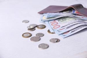 feche o dinheiro na carteira na mesa foto