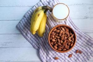 amêndoas, bananas e um copo de leite na mesa foto