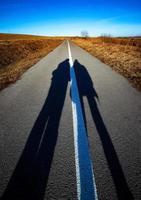 longas sombras de pessoas na estrada foto