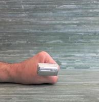 segurando um aparelho de barbear em uma mão foto