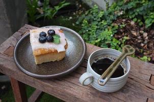 café com um pedaço de bolo na mesa de madeira foto
