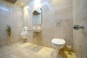 banheiro bege moderno com vaso sanitário, pia, espelho e bidê foto