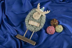 Rosquinhas doces coloridas com um brinquedo de cervo de natal foto