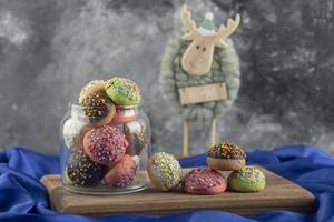 Donuts doces coloridos com um brinquedo de cervo de natal foto