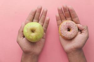 segurando uma maçã verde e uma pequena rosquinha no fundo rosa