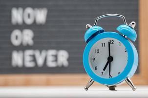 despertador analógico azul em fundo de texto em inglês que diz agora ou nunca