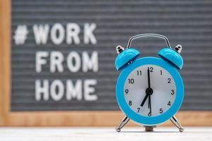 despertador vintage no fundo de um texto em inglês que diz trabalhe em casa foto