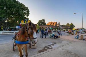lampang, tailândia 2021- carruagem de cavalos estacionada em frente ao templo wat phra de lampang luang