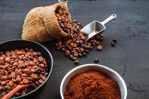 grãos de café e café moído em uma mesa escura