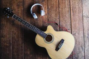 fones de ouvido e uma guitarra
