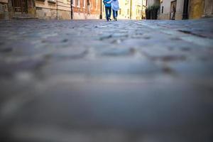 um rapaz e uma rapariga numa velha rua de paralelepípedos na europa