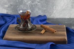 um copo de chá com paus de canela em uma tábua de madeira foto