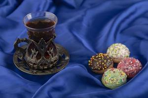 rosquinhas doces coloridas com uma xícara de chá foto