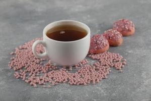 rosquinhas rosadas com uma xícara de chá foto