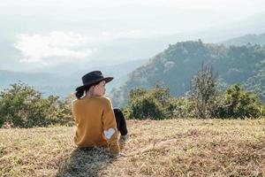 mulher sentada em uma montanha foto