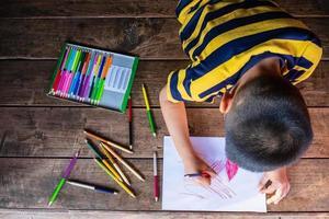 menino desenhando com lápis de colorir