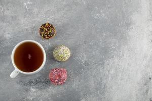 uma xícara de chá branco com pequenos donuts deliciosos foto