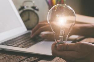uma pessoa segurando uma lâmpada ao lado de um laptop, conceito de novas ideias