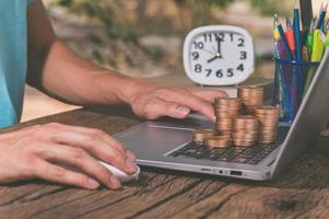 uma pessoa usando um computador com uma pilha de moedas, conceito de ganhar dinheiro online