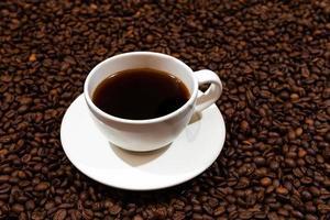 caneca de café branca no fundo de grãos de café foto