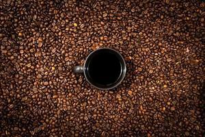 vista superior da caneca de café preta no fundo dos grãos de café foto