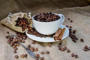 caneca de café branca cheia de grãos de café orgânico e paus de canela em tecido de linho foto