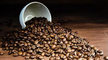 grão de café saindo de uma caneca branca na mesa de madeira foto