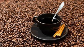 caneca de café preta e paus de canela no fundo de grãos de café foto