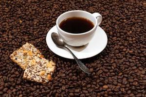 caneca de café branco e biscoitos no fundo de grãos de café foto