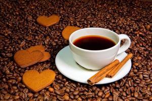 caneca de café branco, paus de canela e biscoitos de gengibre em forma de coração foto