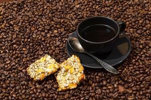 caneca de café preta e biscoitos no fundo de grãos de café foto