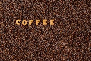 a palavra café feito com letras de biscoito em um fundo escuro de grãos de café