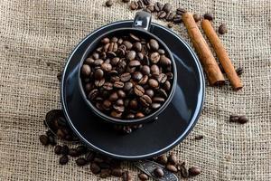 caneca de café preta cheia de grãos de café orgânico e paus de canela em tecido de linho foto