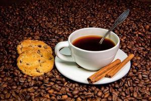 caneca de café branco, paus de canela e biscoitos no fundo de grãos de café foto